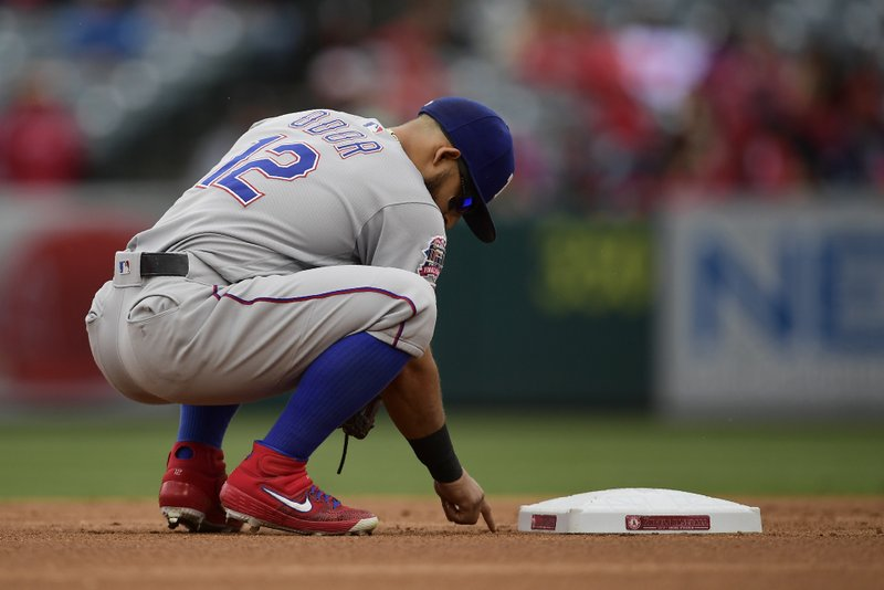 Texas Rangers second baseman Rougned Odor writes on the ground behind second base before a baseball game against the Los Angeles Angels, Sunday, May 26, 2019, in Anaheim, Calif. (AP Photo/Mark J. Terrill)