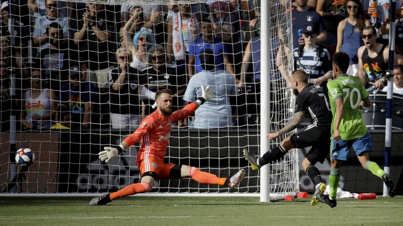 Sporting Kansas City forward Johnny Russell (7) gets the ball past Seattle Sounders goalkeeper Stefan Frei, left, to score a goal during the first half of an MLS soccer match Sunday, May 26, 2019, in Kansas City, Kan. (AP Photo/Charlie Riedel)