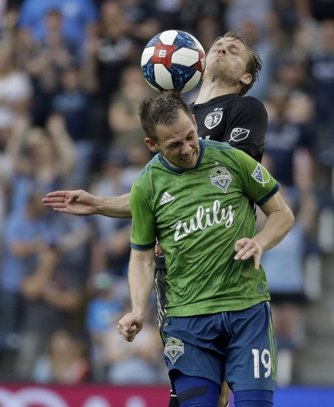 Seattle Sounders forward Harrison Shipp (19) and Sporting Kansas City defender Seth Sinovic, top, battle to control the ball during the second half of an MLS soccer match Sunday, May 26, 2019, in Kansas City, Kan. (AP Photo/Charlie Riedel)