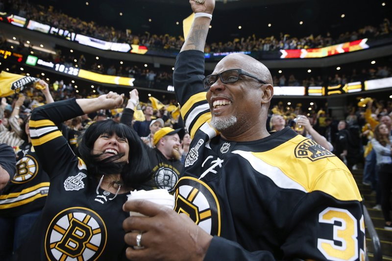 Boston Bruins fans celebrate their team's goal against the St. Louis Blues during the third period in Game 1 of the NHL hockey Stanley Cup Final, Monday, May 27, 2019, in Boston. (AP Photo/Michael Dwyer)