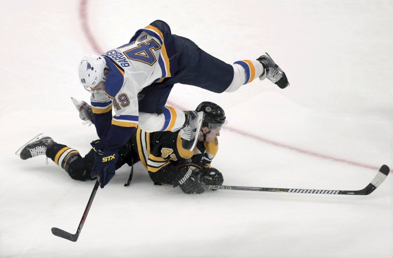 St. Louis Blues' Ivan Barbashev, top, of Russia, trips over Boston Bruins' Torey Krug during the third period in Game 1 of the NHL hockey Stanley Cup Final, Monday, May 27, 2019, in Boston. (AP Photo/Charles Krupa)
