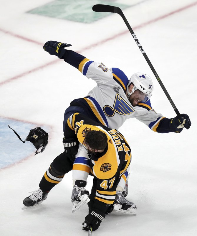 St. Louis Blues' David Perron (57) rips the helmet off Boston Bruins' Torey Krug (47) during the third period in Game 1 of the NHL hockey Stanley Cup Final, Monday, May 27, 2019, in Boston. (AP Photo/Charles Krupa)