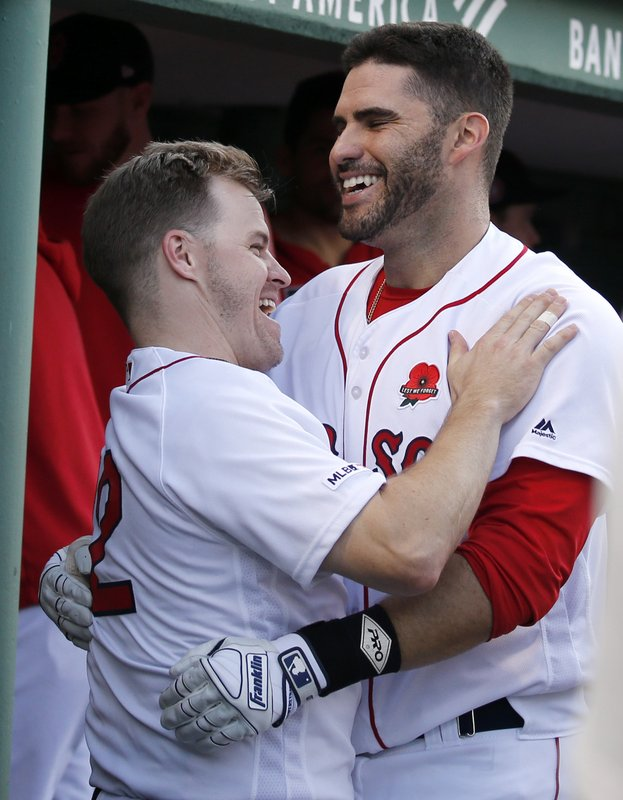 Boston Red Sox's Brock Holt, left, celebrates with J.D. Martinez in the dugout after Martinez hit a home run during the sixth inning of a baseball game against the Cleveland Indians, Monday, May 27, 2019, in Boston. (AP Photo/Mary Schwalm)