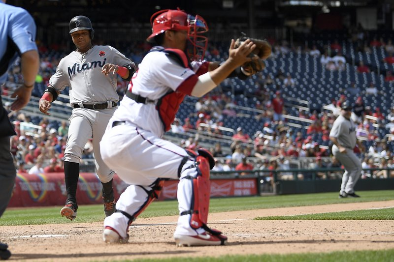 Miami Marlins' Starlin Castro, left, comes in to score on sacrifice fly by Miguel Rojas during the eighth inning of a baseball game against Washington Nationals catcher Kurt Suzuki, right, Monday, May 27, 2019, in Washington. (AP Photo/Nick Wass)