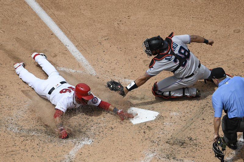Washington Nationals' Gerardo Parra, left, slides home to score against Miami Marlins catcher Jorge Alfaro (38) on a single by Max Scherzer during the fifth inning of a baseball game, Monday, May 27, 2019, in Washington. (AP Photo/Nick Wass)