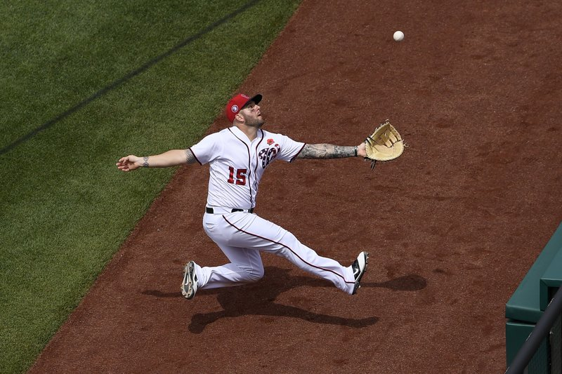 Washington Nationals first baseman Matt Adams pursues a pop up by Miami Marlins' Starlin Castro but was unable to catch it in foul territory during the sixth inning of a baseball game, Monday, May 27, 2019, in Washington. (AP Photo/Nick Wass)