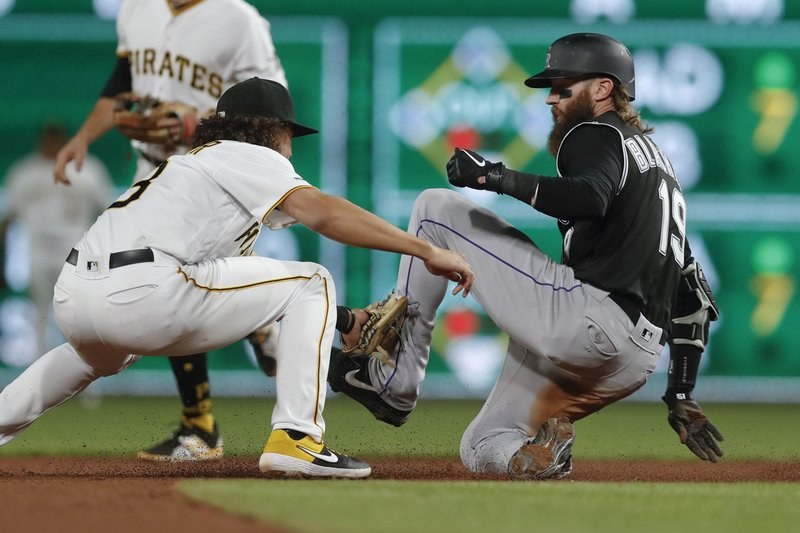 Colorado Rockies' Charlie Blackmon, righty, is tagged out by Pittsburgh Pirates shortstop Cole Tucker on a steal attempt during the seventh inning of a baseball game Tuesday, May 21, 2019, in Pittsburgh. The Rockies won 5-0. (AP Photo/Keith Srakocic)