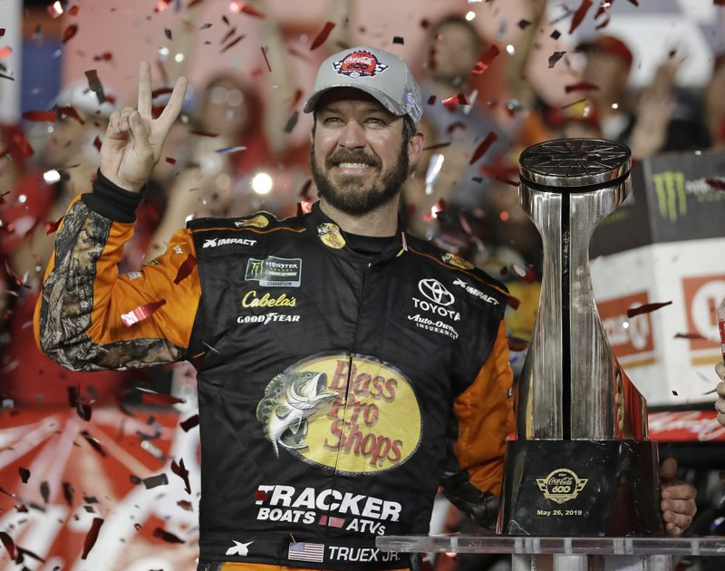 Martin Truex Jr. poses with the trophy in Victory Lane after winning the NASCAR Cup Series auto race at Charlotte Motor Speedway in Concord, N.C., Sunday, May 26, 2019. (AP Photo/Chuck Burton)