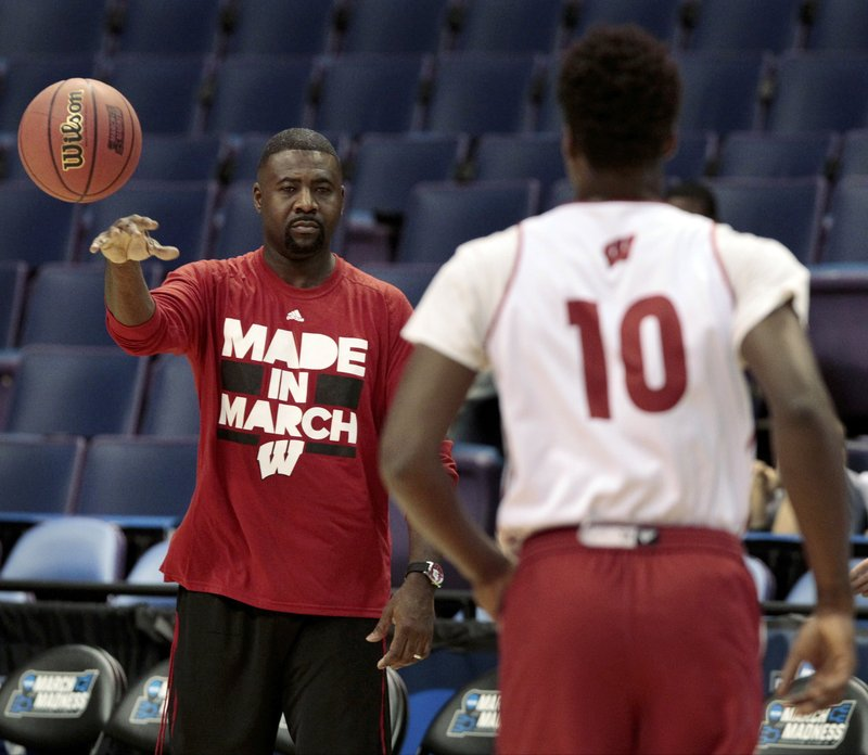 In this March 17, 2016, photo, Wisconsin NCAA college basketball assistant coach Howard Moore, left, passes to forward Nigel Hayes during an open practice at the Scottrade Center in St. Louis, Mo. The University of Wisconsin says the wife and daughter of men's basketball assistant coach Howard Moore were killed in a Michigan automobile accident. Wisconsin's athletic department said Moore's wife, Jennifer, and their daughter, Jaidyn, were killed in the crash on M-14 early Saturday, May 25, 2019, in Washtenaw County's Superior Township. Michigan State Police Lt. Darren Green says Howard Moore suffered third-degree burns but his injuries were not considered life-threatening, and his son had minor injuries. (M.P King/Wisconsin State Journal via AP)