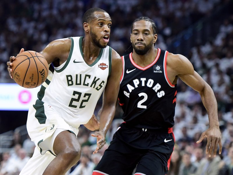 Milwaukee Bucks forward Khris Middleton (22) drives as Toronto Raptors forward Kawhi Leonard (2) defends during the first half in Game 1 of the NBA basketball playoffs Eastern Conference final in Milwaukee on Wednesday, May 15, 2019. (Frank Gunn/The Canadian Press via AP)