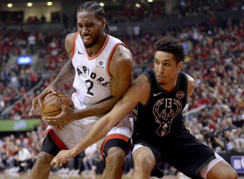 Toronto Raptors forward Kawhi Leonard (2) controls the ball under pressure from Milwaukee Bucks guard Malcolm Brogdon (13) during the second half of Game 6 of the NBA basketball playoffs Eastern Conference finals Saturday, May 25, 2019, in Toronto. (Nathan Denette/The Canadian Press via AP)