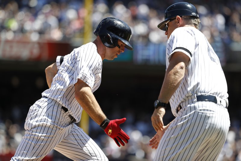 New York Yankees' Brett Gardner celebrates with third base coach Phil Nevin after hitting a two-run home run against the San Diego Padres during the second inning of a baseball game, Monday, May 27, 2019, in New York. Yankees' Gio Urshela also scored. (AP Photo/Michael Owens)