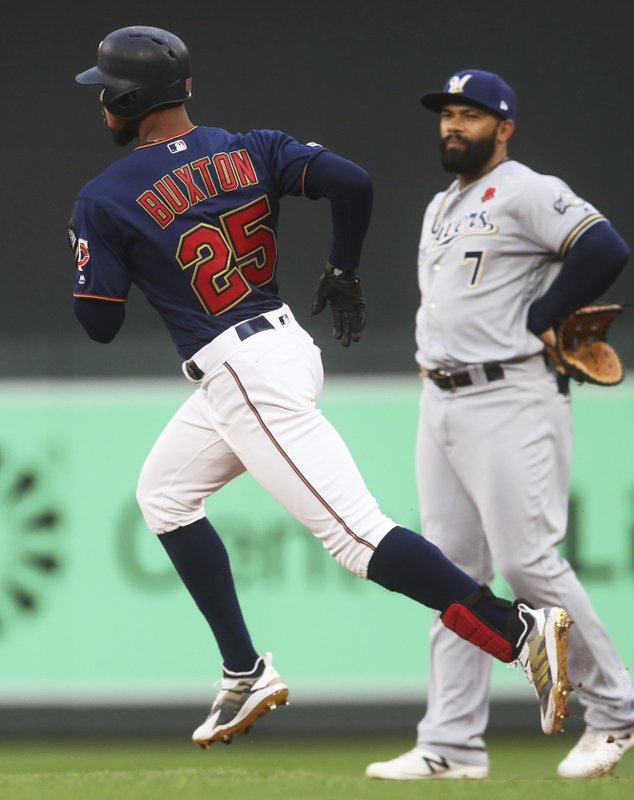 Minnesota Twins' Byron Buxton, left, runs past Milwaukee Brewers first baseman Eric Thames while rounding the bases on a three-run home run off Brewers' Gio Gonzalez in the second inning of a baseball game Monday, May 27, 2019, in Minneapolis. (AP Photo/Jim Mone)