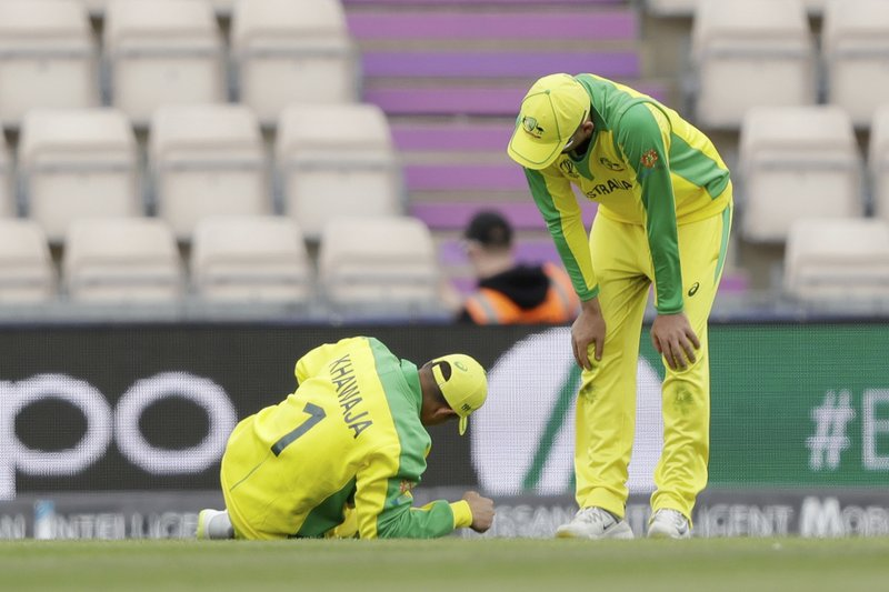Australia's Usman Khawaja, left, lies down with an injury he picked up fielding before he was helped to limp off the field of play during the Cricket World Cup warm-up match between Australia and Sri Lanka at the Hampshire Bowl in Southampton, England, Monday, May 27, 2019. (AP Photo/Matt Dunham)