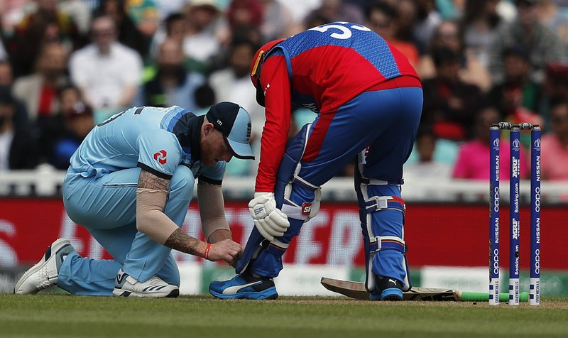 England's Ben Stokes, left, ties the shoe laces of Afghanistan's Aftab Alam during the Cricket World Cup warm up match between England and Afghanistan at the Oval in London, Monday, May 27, 2019. (AP Photo/Frank Augstein)