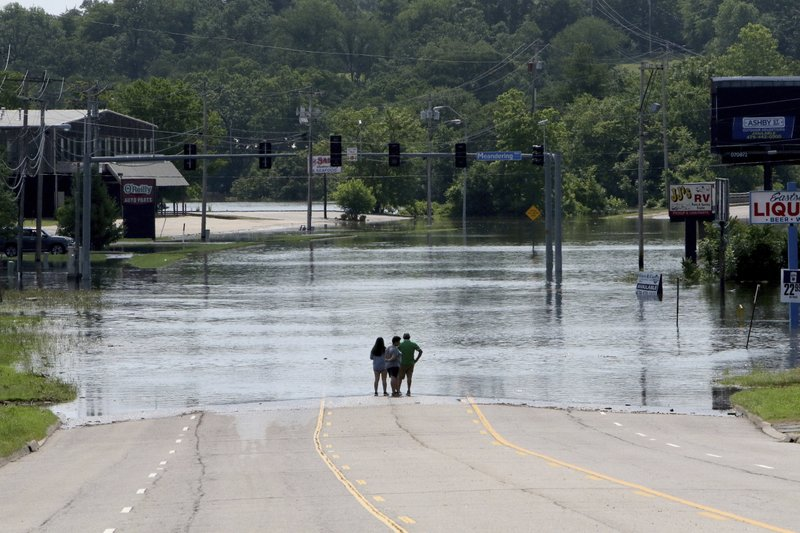 People stand in the middle of Rogers Avenue and look out over the flooded Massard Creek at the intersection of Meandering Way and Rogers Avenue, in Fort Smith, Ark., Saturday, May 25, 2019. (Jamie Mitchell/The Southwest Times Record via AP)