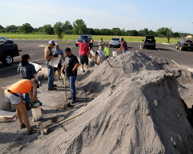 Volunteers fill sand bags at the soccer field parking lot in Chaffee Crossing, Ark., Saturday, May 25, 2019, for distribution throughout the area for flood prone areas around homes. (Jamie Mitchell/The Southwest Times Record via AP)