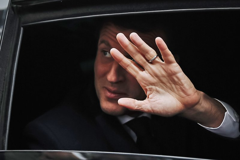 French President Emmanuel Macron waves from his car as he leaves his house after voting in the European elections in Le Touquet, northern France, Sunday May 26, 2019. France is looking at an epic battle between pro-EU centrist President Emmanuel Macron and anti-immigration, far-right flagbearer Marine Le Pen in the European Parliament vote, a duel over Europe's basic values. (AP Photo/Kamil Zihnioglu)