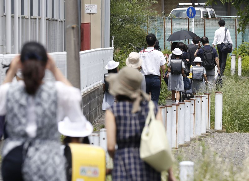 CARITAS Elementary School students leave their school with parents following an attack in Kawasaki, near Tokyo Tuesday, May 28, 2019. A man swinging a knife attacked commuters waiting at a crowded bus stop just outside Tokyo during Tuesday morning's rush hour, wounding a number of people, including children, Japanese authorities said. (Shinji Kita/Kyodo News via AP)