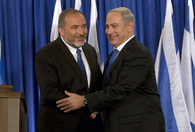 FILE - In this Oct. 25, 2012 file photo, Israeli Prime Minister Benjamin Netanyahu, right, and former Israeli Defense Minister Avigdor Lieberman shake hands in front of the media after giving a statement in Jerusalem. Netanyahu is facing the possibility of having to fight a second election this year, as he struggles to form a coalition government. With a looming deadline, Israel's newly elected parliament began drafting a bill on Monday to dissolve itself. (AP Photo/Bernat Armangue, File)