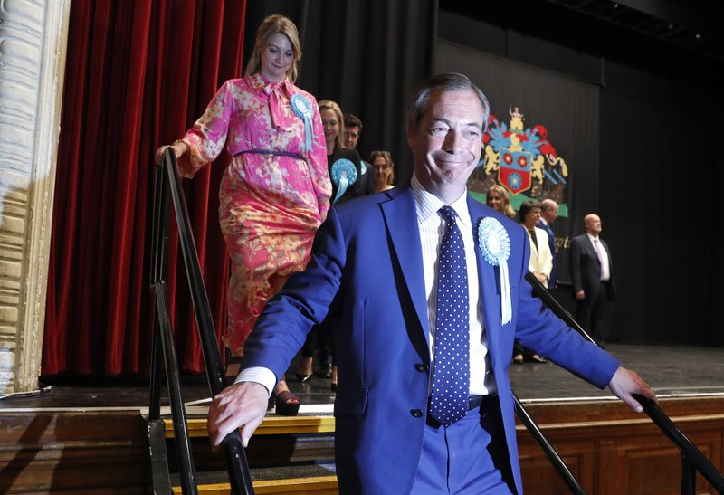 Brexit Party leader Nigel Farage walks off the stage after results were announced at the counting center for the European Elections for the South East England region, in Southampton, England, early Monday, May 27, 2019. (AP Photo/Alastair Grant)