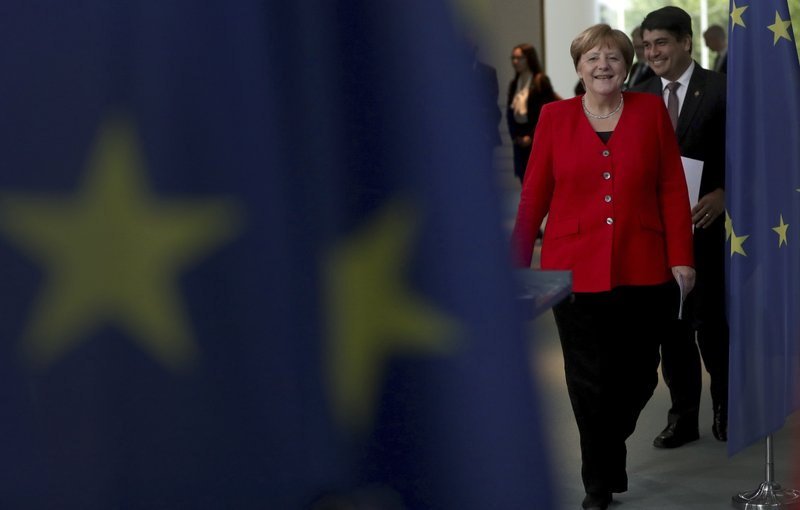 German Chancellor Angela Merkel, front, and the president of Costa Rica, Carlos Alvarado Quesada, rear, arrive for a joint statement prior to a meeting at the Chancellery in Berlin, Germany, Monday, May 27, 2019. (AP Photo/Michael Sohn)