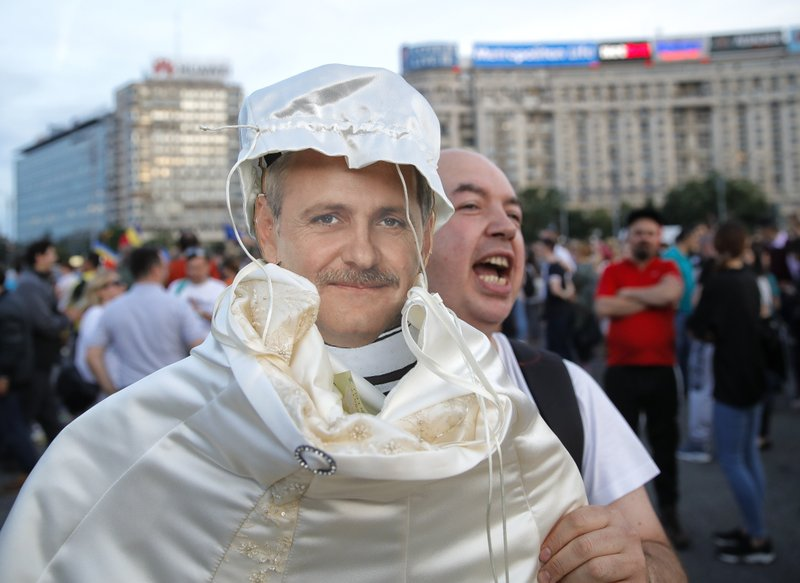 A man shouts holding a cardboard depiction of Liviu Dragnea, the leader of the ruling Social Democratic party, as hundreds celebrate his sentencing to prison outside the government headquarters in Bucharest, Romania, Monday, May 27, 2019. Romania's most powerful politician was sentenced Monday to 3 and a half years in prison for official misconduct in a graft case. (AP Photo/Vadim Ghirda)