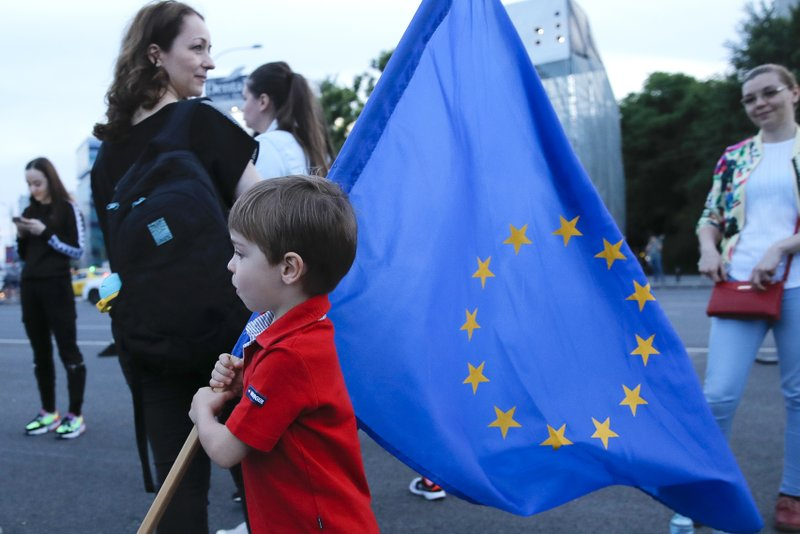 A child holds a European Union flag as hundreds celebrate the sentencing to prison of Liviu Dragnea, the leader of the ruling Social Democratic party, outside the government headquarters in Bucharest, Romania, Monday, May 27, 2019. Romania's most powerful politician was sentenced Monday to 3 and a half years in prison for official misconduct in a graft case.(AP Photo/Vadim Ghirda)