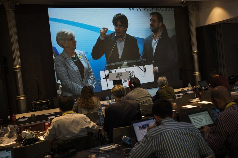Former regional Catalan President Carles Puigdemont appears on a screen during a video conference from Brussels, at the party headquarters in Barcelona, Catalonia, Spain, Sunday, May 26, 2019. Former Catalan regional president Carles Puigdemont, his ex-No. 2 Oriol Junqueras and former Catalan Cabinet member Toni Comín all won seats for separatist parties in Sunday's EU vote. That's according to provisional results released by Spain's Interior Ministry with 85% of the votes counted. (AP Photo/Emilio Morenatti)