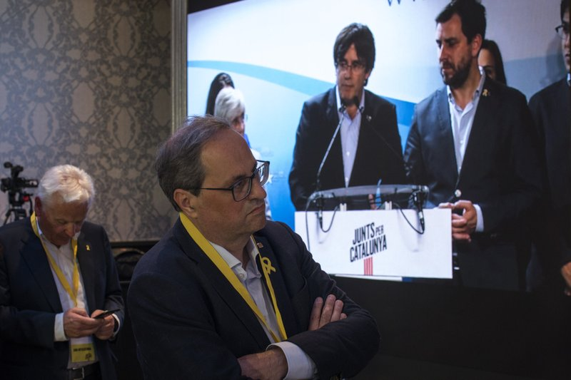 Regional Catalan President Quim Torra, centre, looks at former regional Catalan President Carles Puigdemont appearing on a screen during a video conference from Brussels, at the party headquarters in Barcelona, Catalonia, Spain, Sunday, May 26, 2019. Former Catalan regional president Carles Puigdemont, his ex-No. 2 Oriol Junqueras and former Catalan Cabinet member Toni Comín all won seats for separatist parties in Sunday's EU vote. That's according to provisional results released by Spain's Interior Ministry with 85% of the votes counted. (AP Photo/Emilio Morenatti)