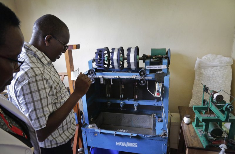 In this photo taken Friday, April 26, 2019, Director of the National Sericulture Research Center, Muo Kasina, demonstrates a silk reeling machine at the center in Thika, Kenya. A growing number of Kenyan farmers are turning to silk production as they move away from traditional cash crops such as coffee, maize, sugarcane and cotton, with the mulberry trees the silkworms need to survive seen as less affected by a changing climate. (AP Photo/Khalil Senosi)