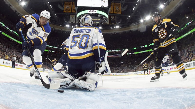 St. Louis Blues' Brayden Schenn (10) stops the puck sliding toward the net behind goaltender Jordan Binnington (50) as Boston Bruins' Patrice Bergeron, right, approaches during the first period in Game 1 of the NHL hockey Stanley Cup Final, Monday, May 27, 2019, in Boston. (Bruce Bennett/Pool via AP)