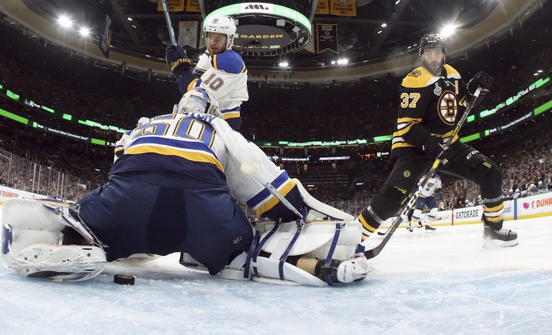 The puck slide toward the net behind goaltender Jordan Binnington (50) as Boston Bruins' Patrice Bergeron, right, approaches during the first period in Game 1 of the NHL hockey Stanley Cup Final, Monday, May 27, 2019, in Boston. (Bruce Bennett/Pool via AP)