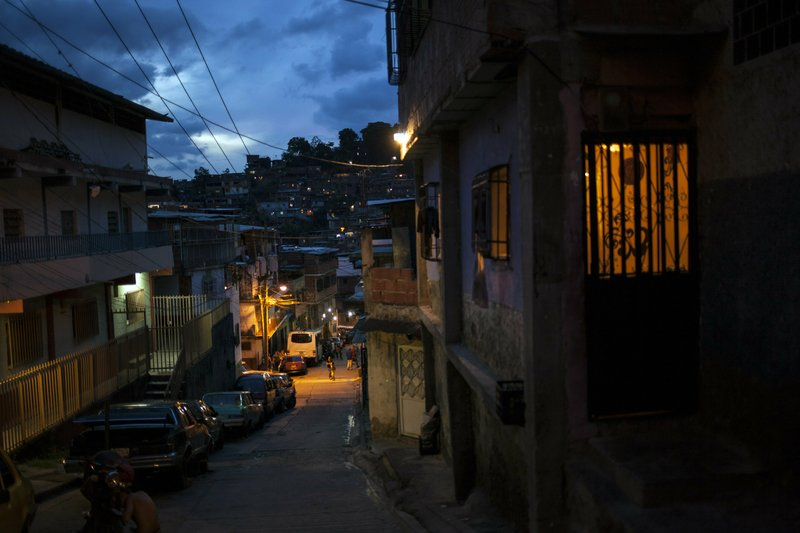 A street goes dark as the sun sets in the Petare slum of Caracas, Venezuela, Saturday, May 25, 201. When night falls, streets in Caracas clear as most residents abide by an undeclared curfew out of fear for their safety.  (AP Photo/Rodrigo Abd)