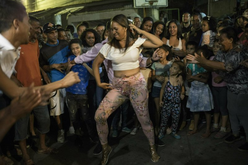 A woman dances with neighbors during a Mother's Day block party in the Petare slum of Caracas, Venezuela, Sunday, May 19, 2019. A decline in armed assaults and killings in Venezuela has a direct link to the economic tailspin that's helped spark a political battle for control of the once-wealthy oil nation. (AP Photo/Rodrigo Abd)