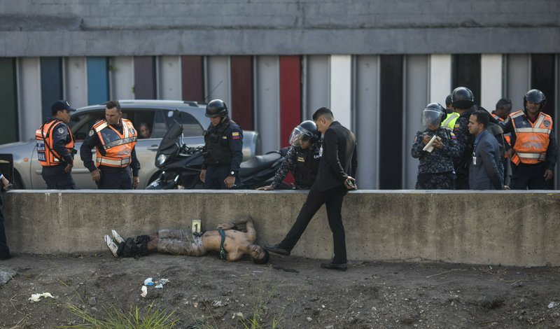 """EDS NOTE: GRAPHIC CONTENT - A police investigator uses his foot to point to the head of a man with his arms and legs bound who was removed from the Guaire River in Caracas, Venezuela, Monday, Feb. 4, 2019. """"Venezuela remains one of the most violent countries in the world,"""" said Dorothy Kronick, who teaches political science at the University of Pennsylvania and has carried out extensive research inside Caracas' slums. """"It has wartime levels of violence _ but no war."""" (AP Photo/Rodrigo Abd)"""