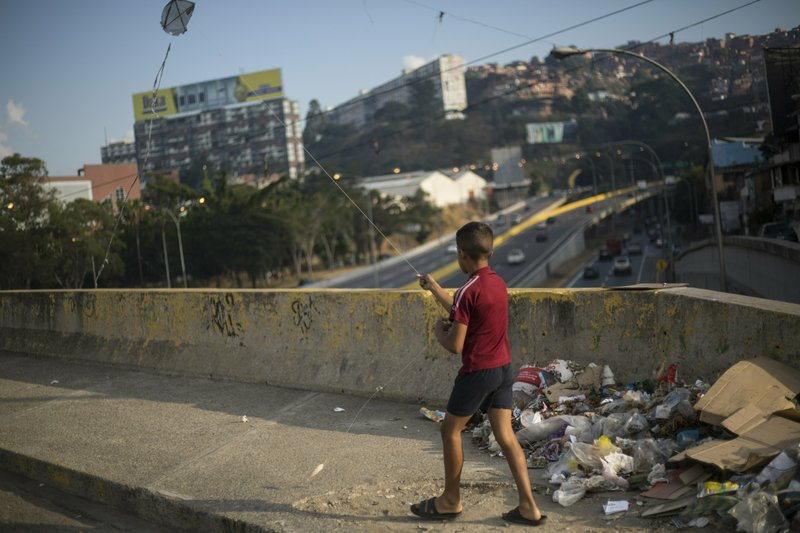 A boy flies a kite in Caracas, Venezuela, Tuesday, Feb. 5, 2019. Earlier this year, opposition leader Juan Guaidó launched a bold campaign with the support of the U.S. and more than 50 nations to oust Chávez's successor, President Nicolás Maduro. However, Guaidó has yet to make good on his promises to restore democracy, spark a robust economy and make the streets safer. (AP Photo/Rodrigo Abd)