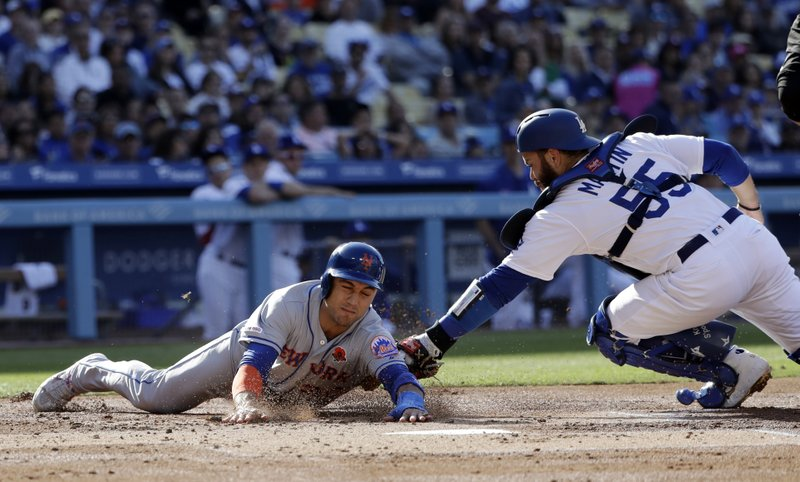 New York Mets' Michael Conforto, left, is tagged out at the plate by Los Angeles Dodgers catcher Russell Martin (55) on a single by Todd Frazier during the first inning of a baseball game Monday, May 27, 2019, in Los Angeles. (AP Photo/Marcio Jose Sanchez)