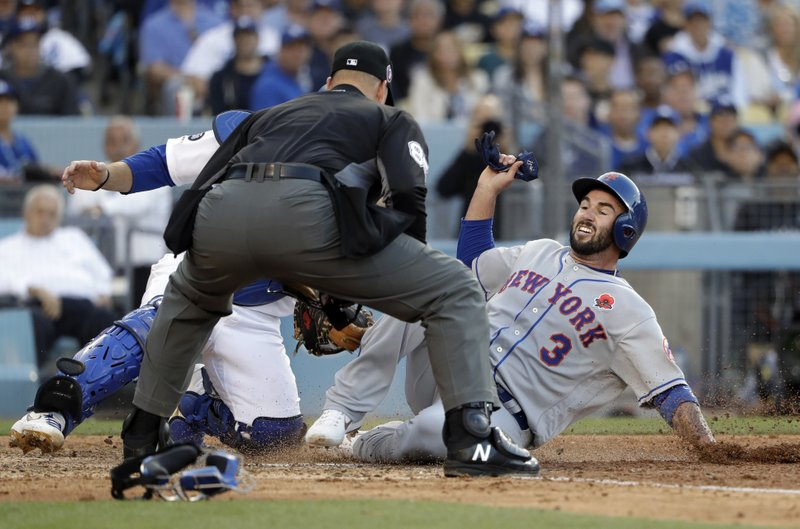 New York Mets' Tomas Nido, right, is tagged by Los Angeles Dodgers catcher Russell Martin as Nido tried to score on a double by Amed Rosario during the fifth inning of a baseball game Monday, May 27, 2019, in Los Angeles. (AP Photo/Marcio Jose Sanchez)