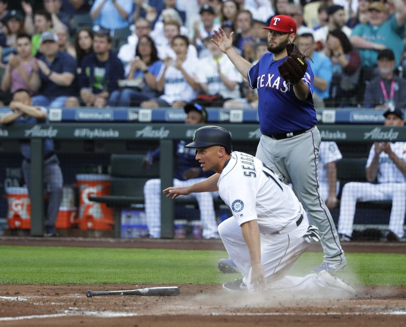 Seattle Mariners' Kyle Seager slides safely home to score on an RBI single hit by Domingo Santana as Texas Rangers starting pitcher Lance Lynn backs up the play during the third inning of a baseball game, Monday, May 27, 2019, in Seattle. (AP Photo/Ted S. Warren)
