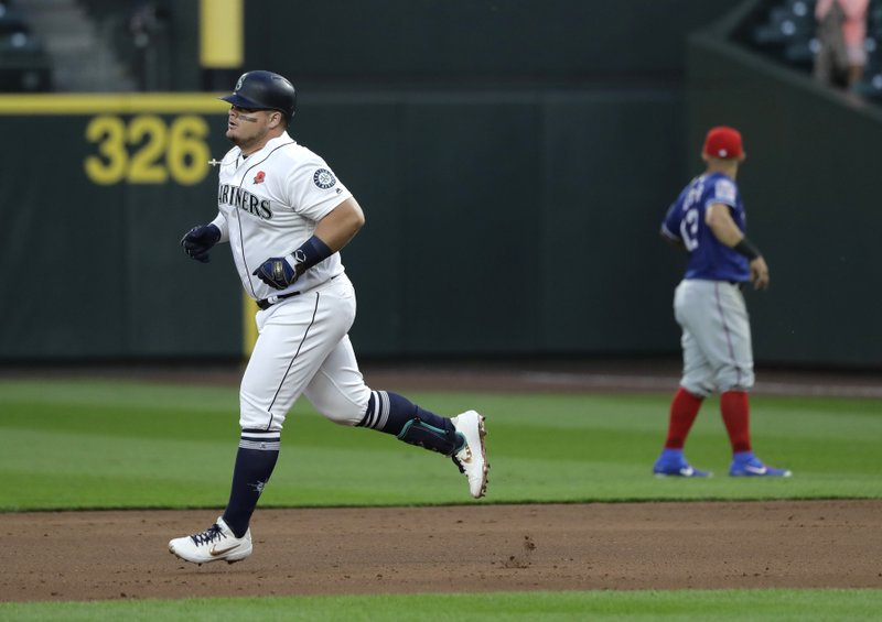 Seattle Mariners' Daniel Vogelbach, left, rounds the bases after he hit a two-run home run against the Texas Rangers during the seventh inning of a baseball game, Monday, May 27, 2019, in Seattle. (AP Photo/Ted S. Warren)