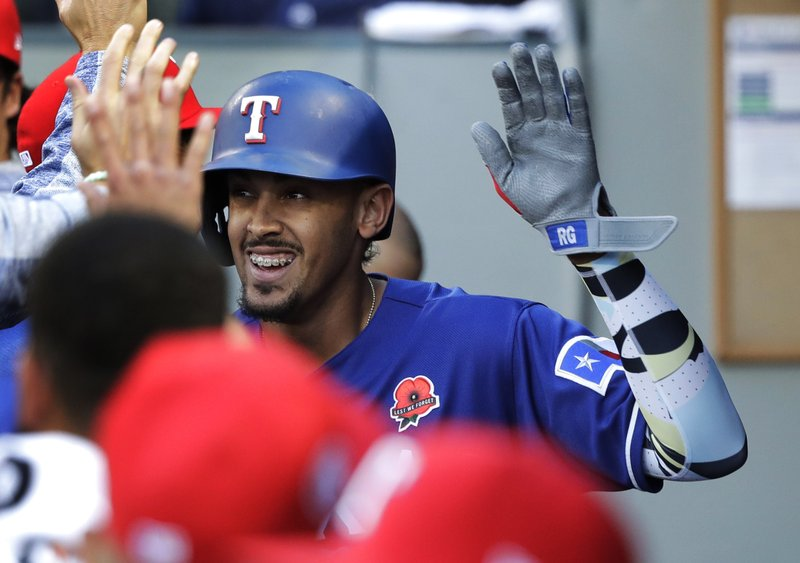 Texas Rangers' Ronald Guzman is greeted in the dugout after he hit a solo home run during the fifth inning of a baseball game against the Seattle Mariners, Monday, May 27, 2019, in Seattle. (AP Photo/Ted S. Warren)