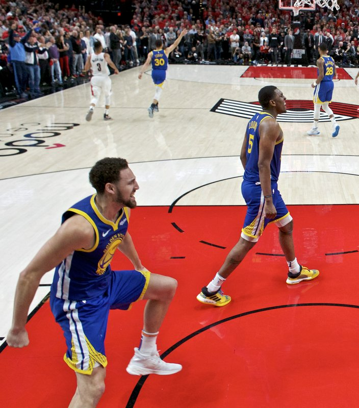 Golden State Warriors guard Klay Thompson, left and center Kevon Looney celebrate at the end of Game 4 of the NBA basketball playoffs Western Conference finals against the Portland Trail Blazers Monday, May 20, 2019, in Portland, Ore. The Warriors won 119-117 in overtime. (AP Photo/Craig Mitchelldyer)