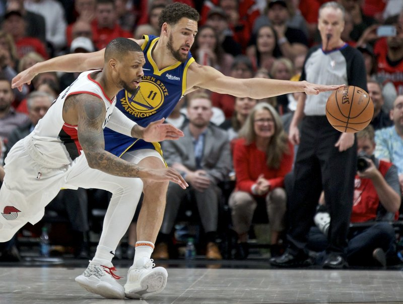 Golden State Warriors guard Klay Thompson, right, and Portland Trail Blazers guard Damian Lillard reach for a loose ball during the second half of Game 4 of the NBA basketball playoffs Western Conference finals Monday, May 20, 2019, in Portland, Ore. The Warriors won 119-117 in overtime. (AP Photo/Craig Mitchelldyer)