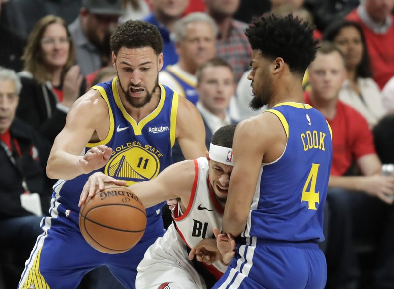 Golden State Warriors guards Klay Thompson, left, and Quinn Cook, right, close in on Portland Trail Blazers guard Seth Curry, center, during the first half of Game 4 of the NBA basketball playoffs Western Conference finals, Monday, May 20, 2019, in Portland, Ore. (AP Photo/Ted S. Warren)