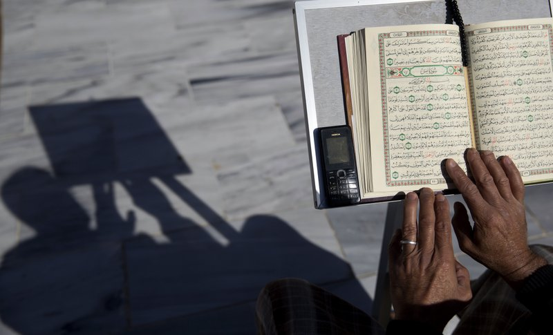 FILE - In this May 8, 2019 file photo, a Palestinian reads verses of the Quran, Islam's holy book, during the month of Ramadan at Al Emari Mosque in Gaza City. The Muslim holy month of Ramadan, with its long days of fasting and prayer meant to draw worshippers closer to God and away from worldly distractions, is being reshaped by technology. People in the Middle East are spending close to 58 million more hours on Facebook and watching more YouTube videos than at any other time of the year, making Ramadan the biggest moment of the year for advertisers. (AP Photo/Hatem Moussa, File)