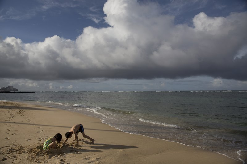 FILE - In this Aug. 25, 2015, file photo two children visiting from China play on Waikiki Beach in Honolulu. Travel from China to the U.S. fell 4.6 percent in the first 10 months of 2018 compared to the same period the prior year, according to U.S. government data. The government hasn't released full-year figures yet, but if the trend holds, it will be the first time since 2003 that Chinese travel to the U.S. fell from the prior year.. (AP Photo/Jae C. Hong, File)