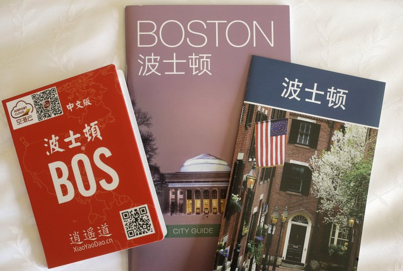 FILE - In this March 23, 2017 photo a pop-up map, left, a city guide, center, and an activities guide, right, all with Chinese translation, rest in a room at the Sheraton Boston Hotel in Boston. Travel from China to the U.S. fell 4.6 percent in the first 10 months of 2018 compared to the same period the prior year, according to U.S. government data. The government hasn't released full-year figures yet, but if the trend holds, it will be the first time since 2003 that Chinese travel to the U.S. fell from the prior year.. (AP Photo/Steven Senne, File)