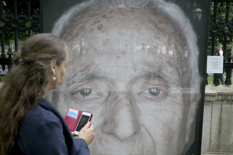 A women looks at destroyed and repaired pictures by the artist Luigi Toscano showing Holocaust survivors in Vienna, Austria, Tuesday, May 28, 2019.  The creator of a photo exhibit of Holocaust survivors in Austria expressed dismay Tuesday that his portraits were slashed and daubed with swastikas in three attacks this month. (AP Photo/Ronald Zak)