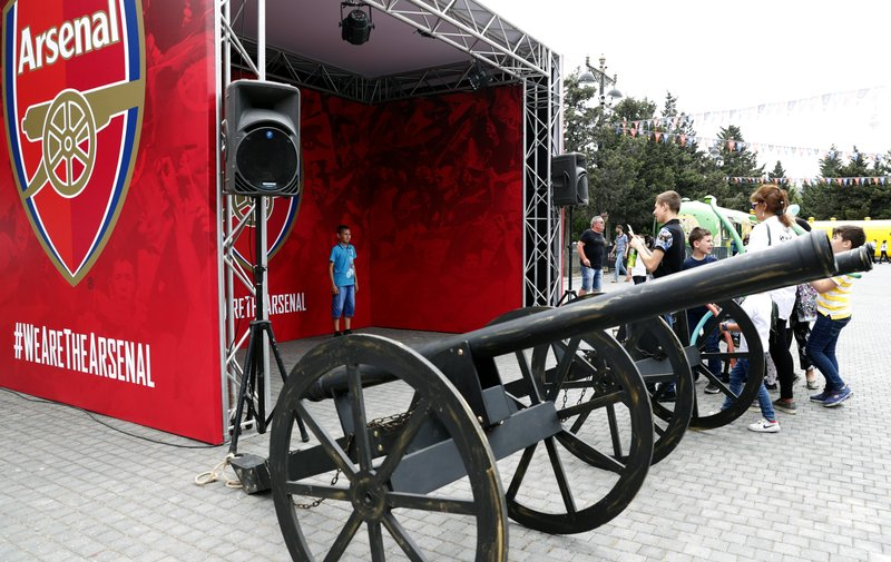 A boy poses for photographs at the Arsenal soccer team booth at the fan area in central Baku, Azerbaijan Tuesday, May 28, 2019. Supporters were arriving in the Azerbaijan capital ahead of Wednesday's Europa League final between English teams Arsenal and Chelsea. (AP Photo/Darko Bandic)